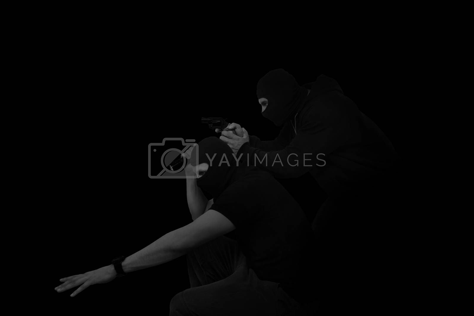 Two masked man with gun and flashlight isolated on black background. Dangerous criminal committing crime.