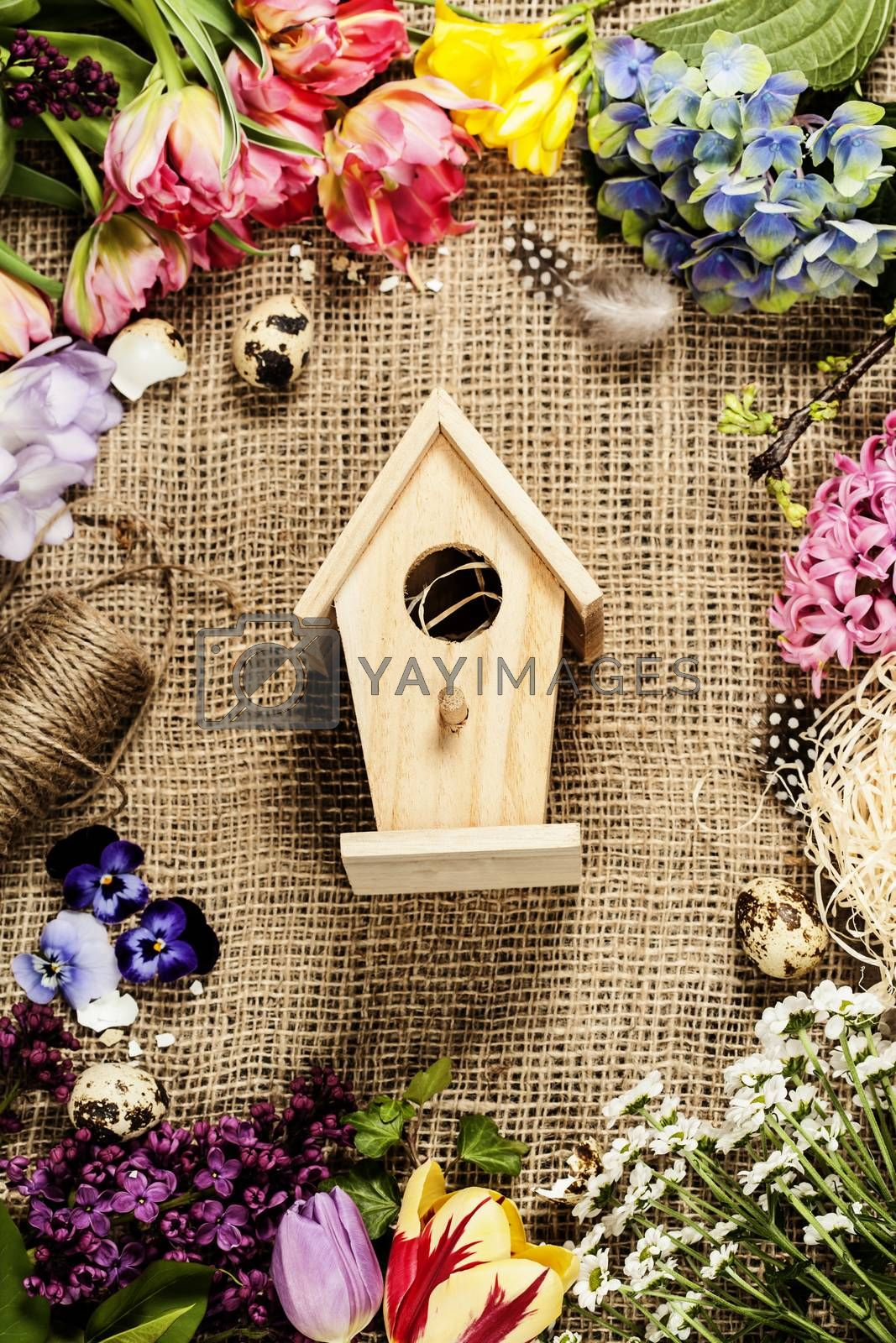 Easter background with bird house, eggs, nest and flowers