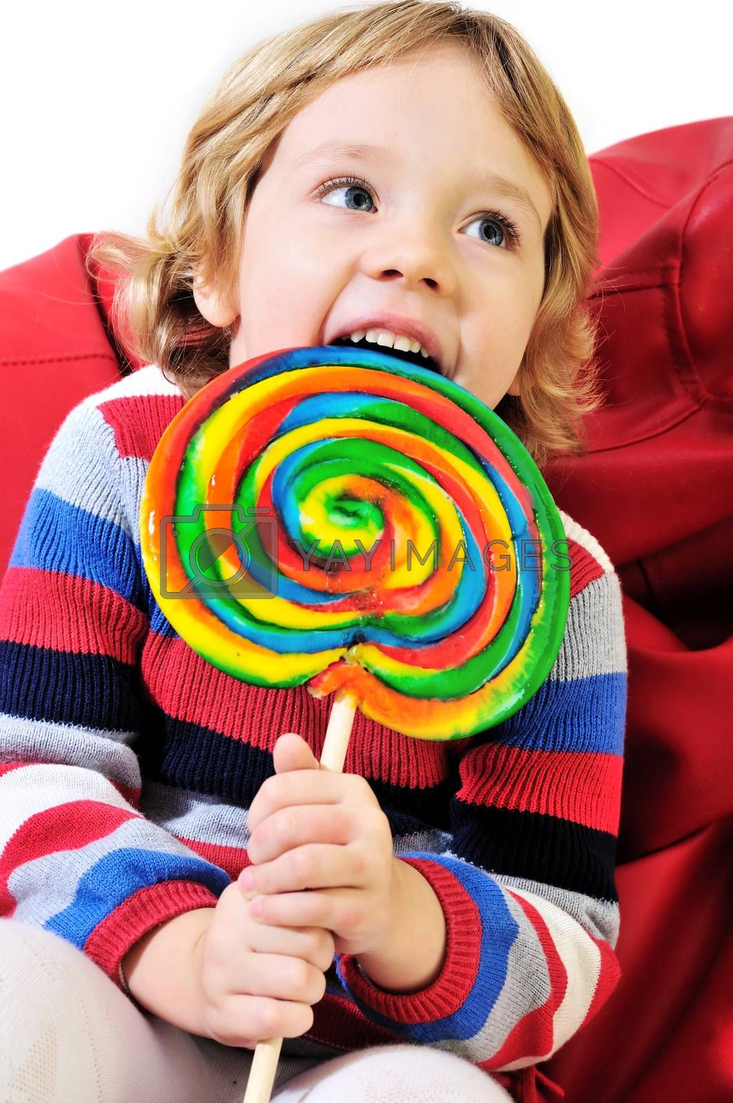 little girl eating big colorful lollipop  and sitting on the arm-chair