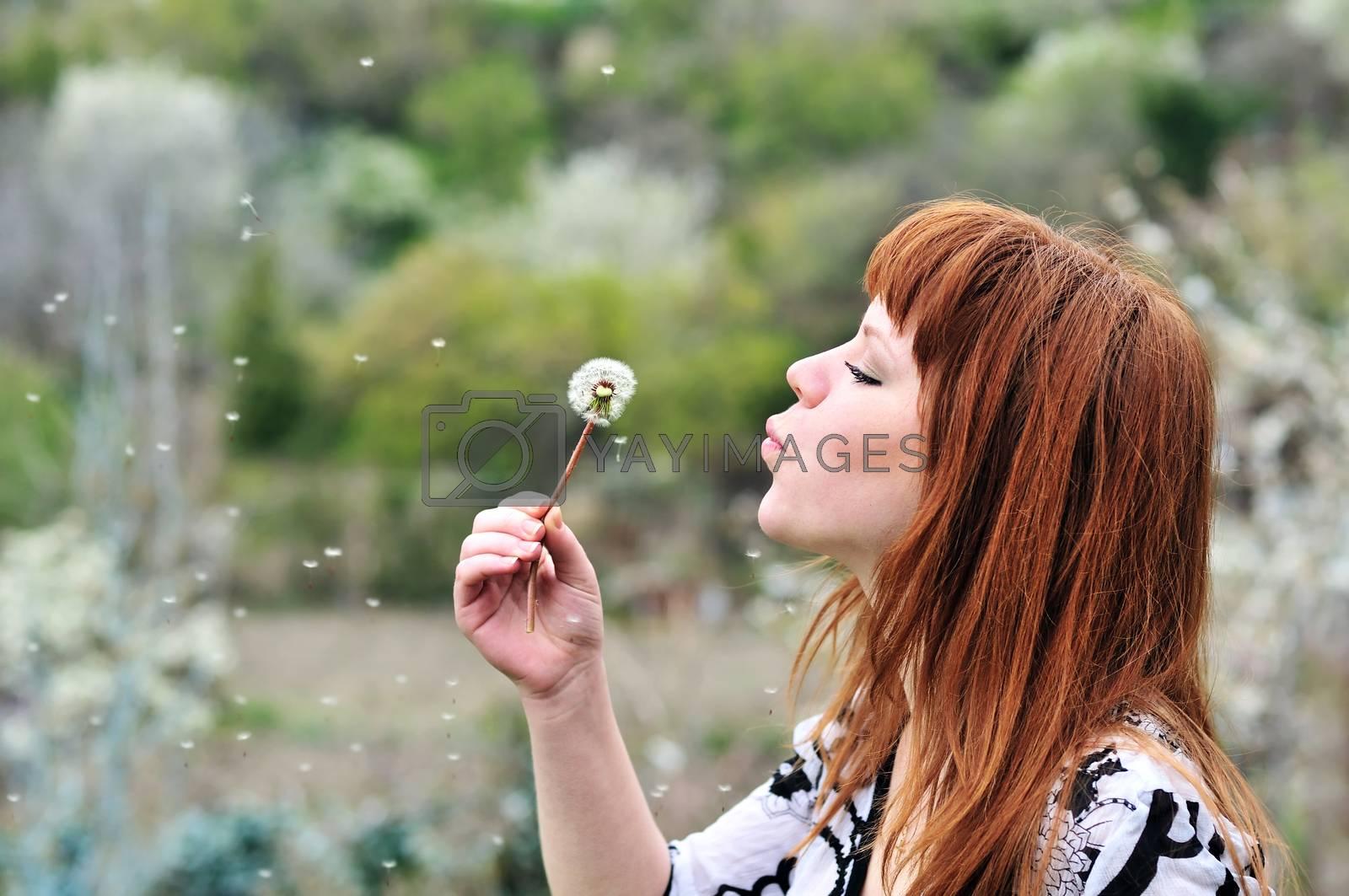 pretty redheaded teen girl blowing on dandelion