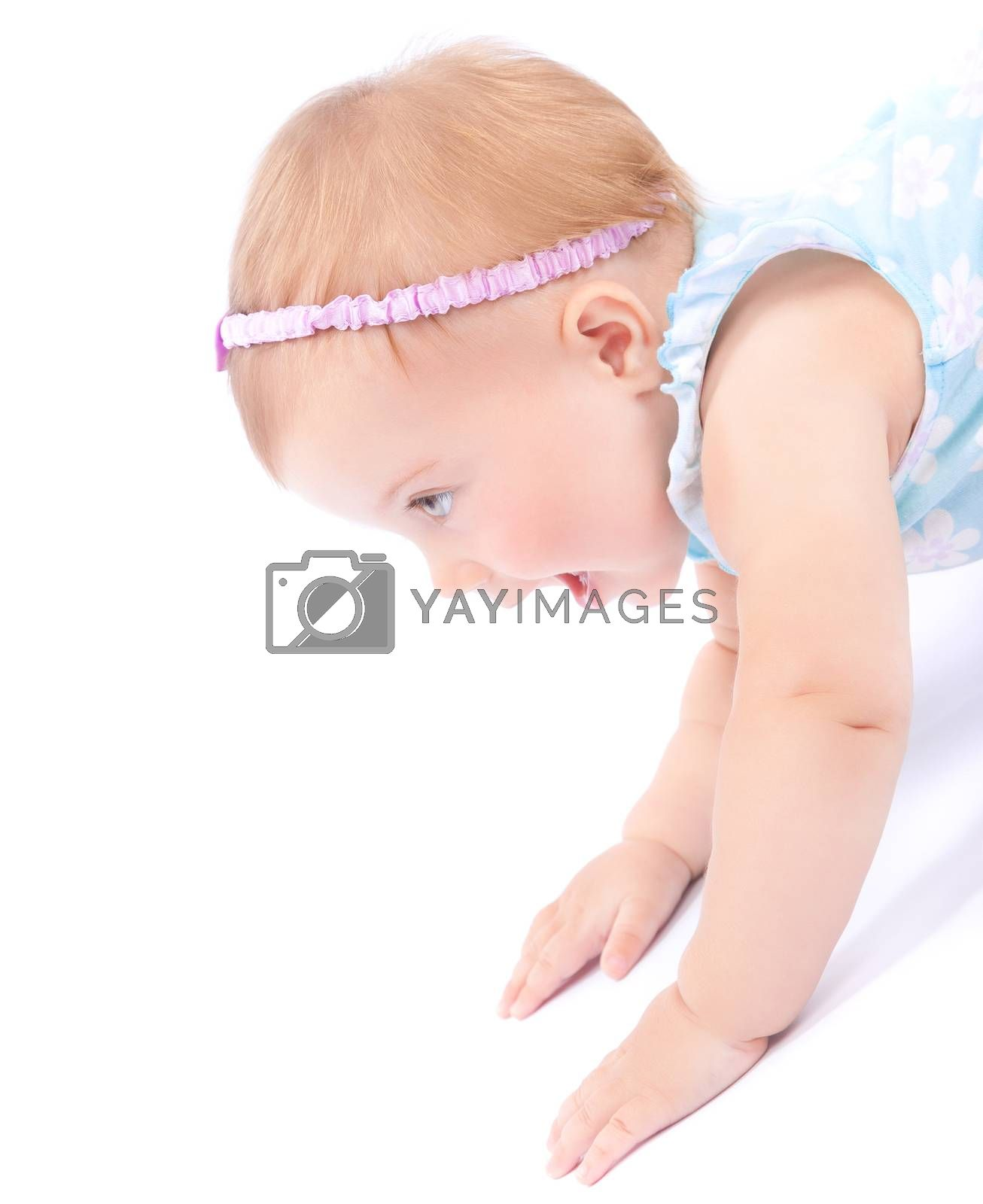 Side view of nice joyful baby girl playing in the studio, isolated on white background, healthy childhood, happiness and enjoyment concept