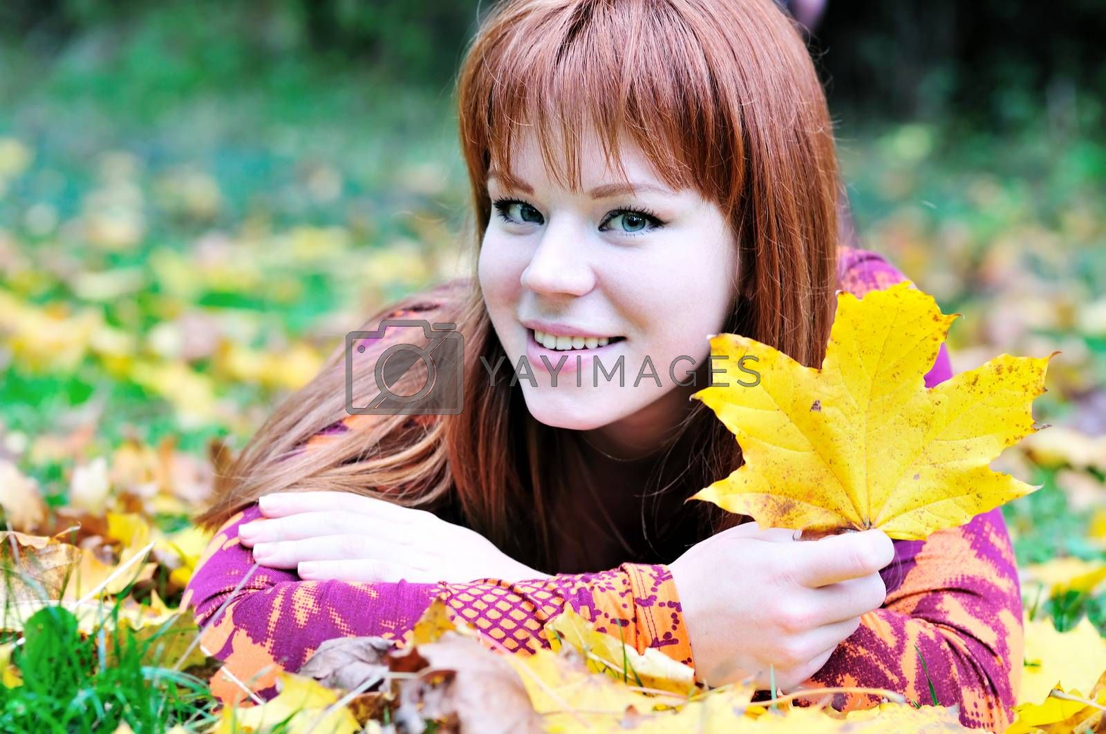 happy redheaded girl laying on the leaves in autumn forest