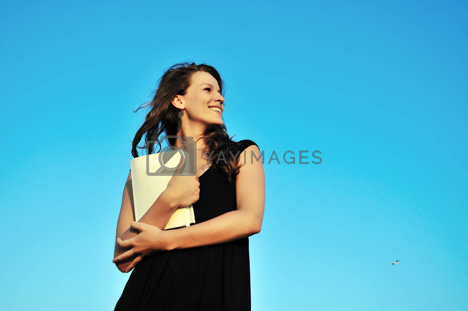 beautiful brunette girl holding book over the sky