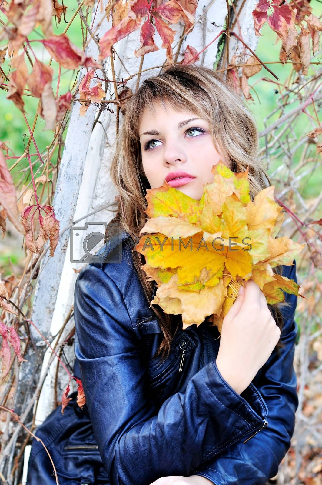 portrait of teen girl wering leather jacket with autumn leaves