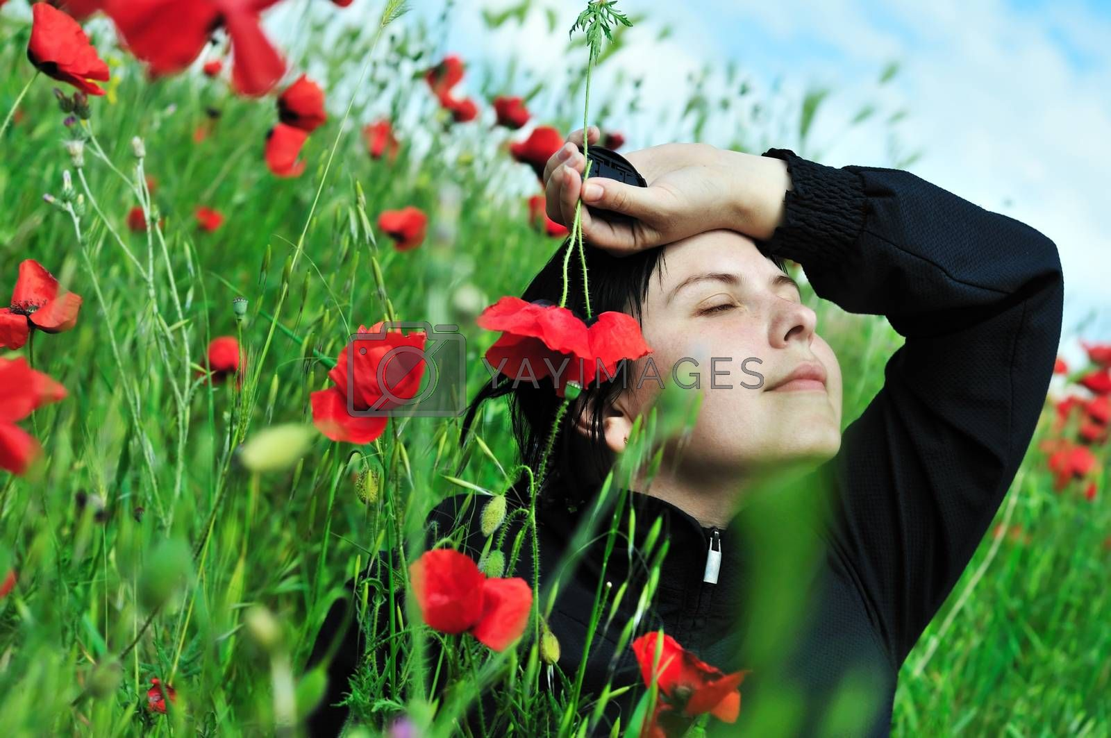 brunette young woman relaxing in the poppies field