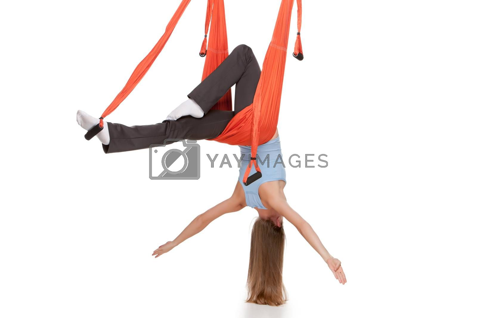Young woman upside down doing anti-gravity aerial yoga in hammock on a seamless white background.