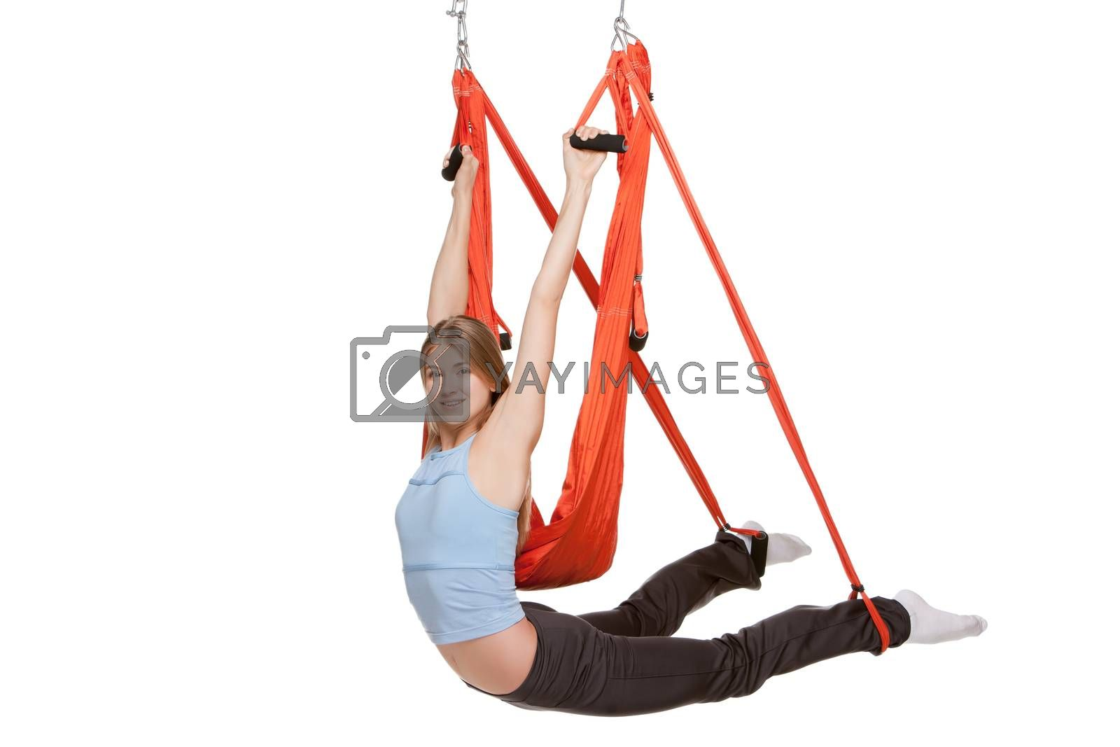 Young woman upside down doing anti-gravity aerial yoga in red hammock on a seamless white background.