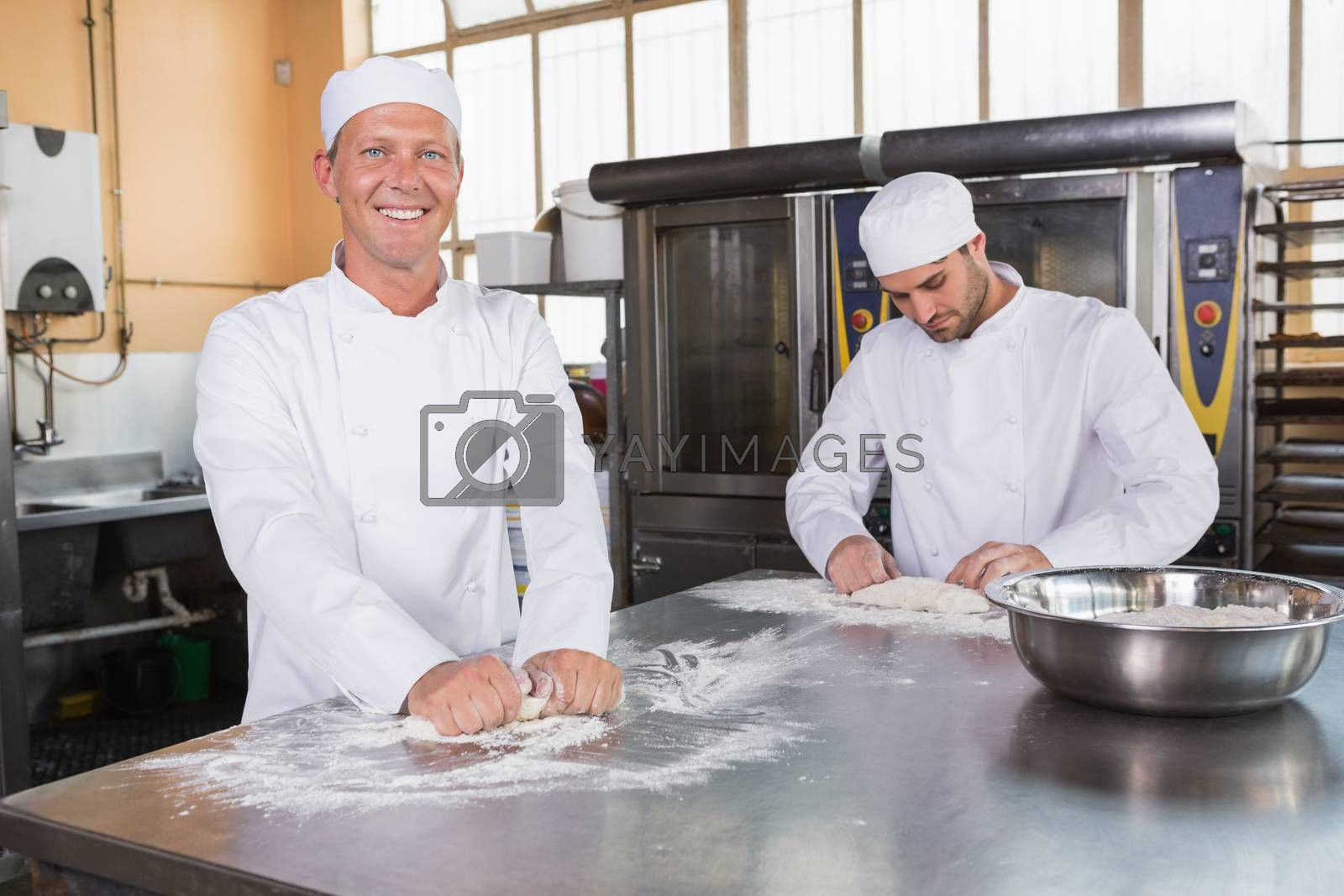Team of bakers working together in commercial kitchen