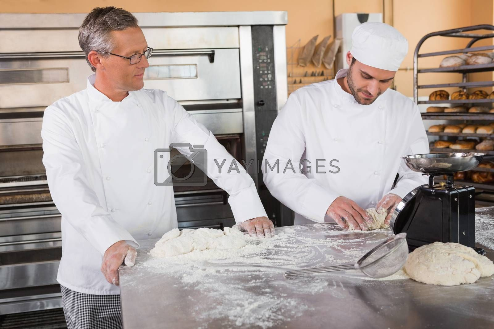 Baker looking his colleague kneading dough in the kitchen of the bakery