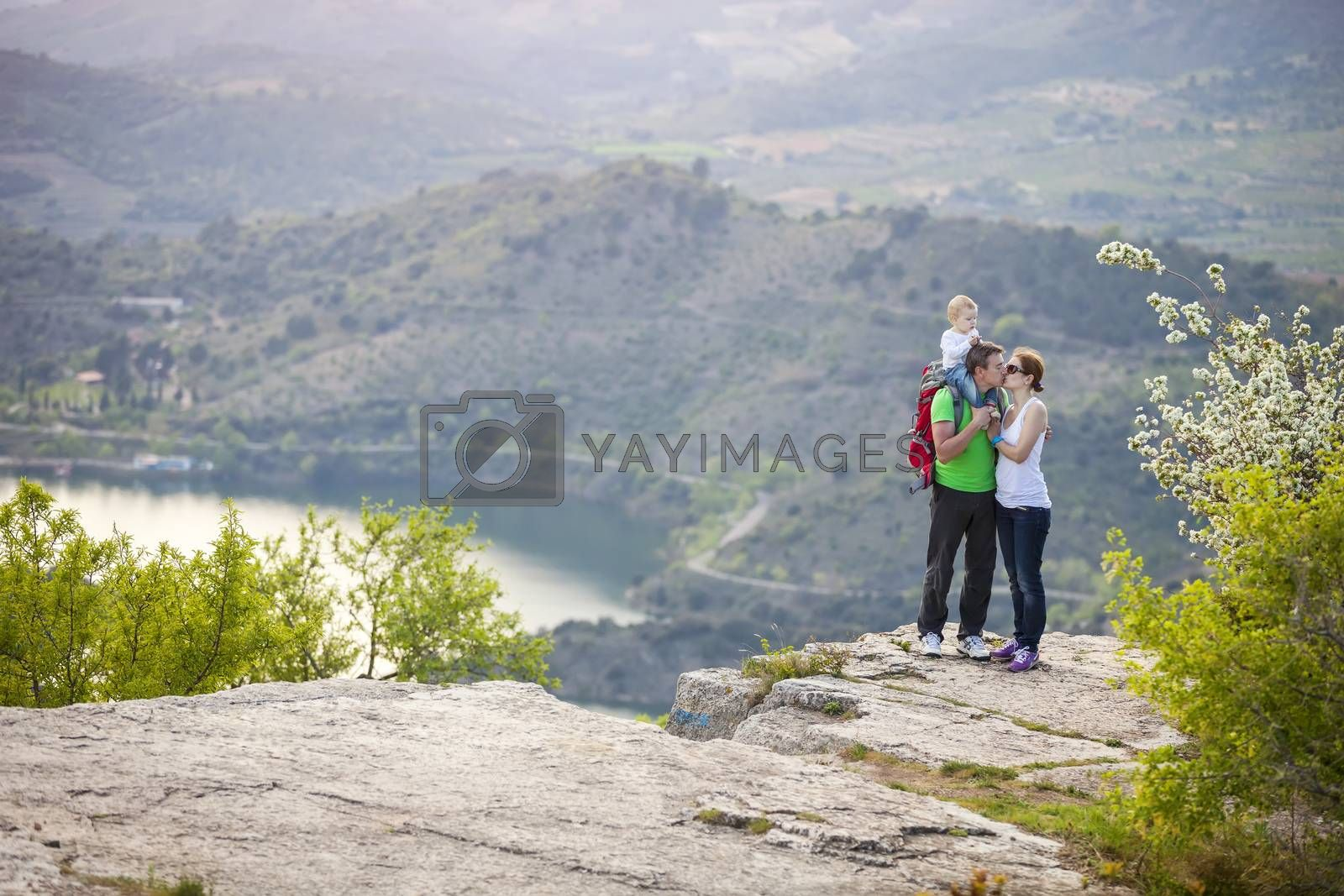Young couple with toddler boy standing on cliff and kissing