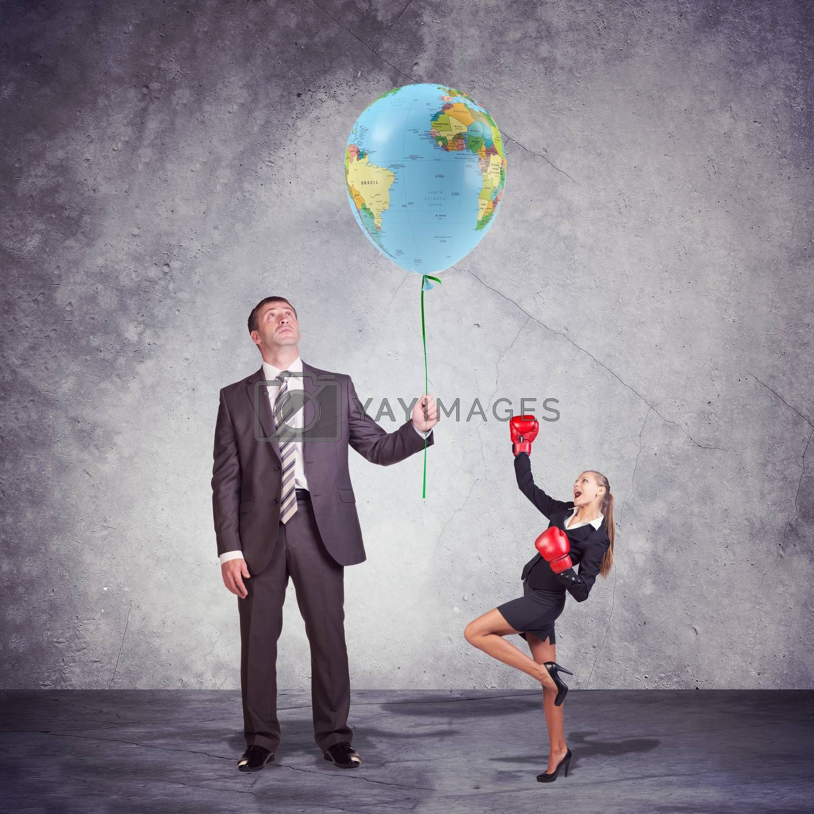 Conceptual Businessman Holding and Looking at the Balloon, with World Map Print, with a Small Businesswoman Posing in Boxing Gloves on the Side. Captured in Studio with Weathered Wall Background