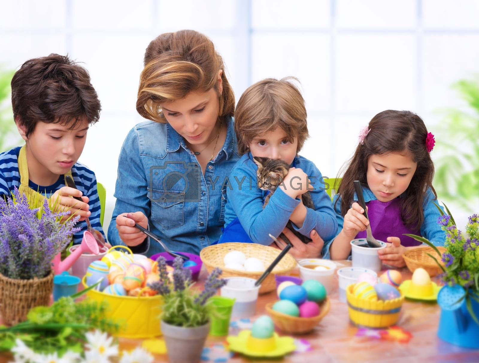 Family portrait in Easter time, creative mother with three cute adorable child coloring eggs at home, making vibrant colorful traditional food