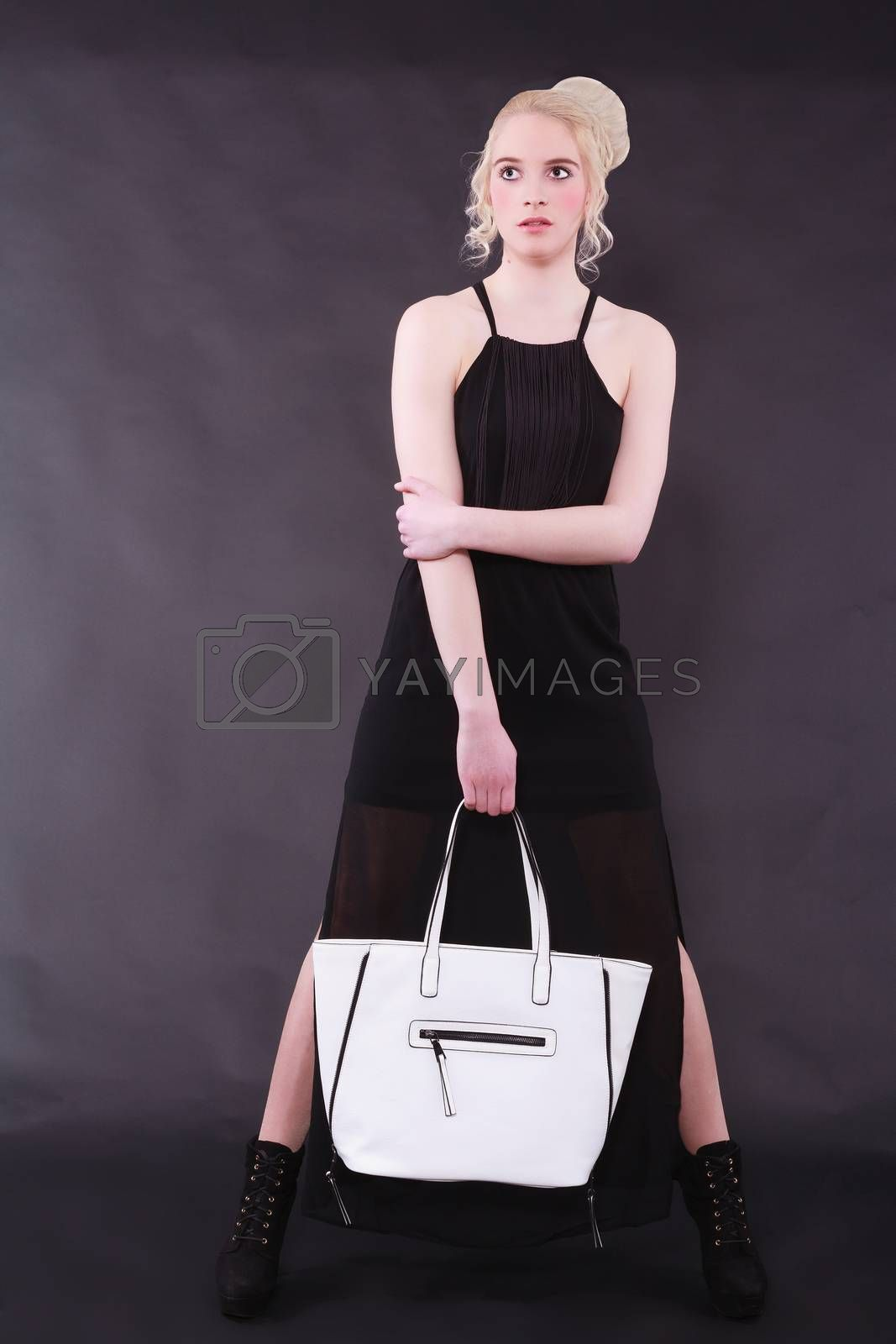 Blonde young model with modern hairstyle stands legs in black dress against a black background and holding a white bag in his hand.