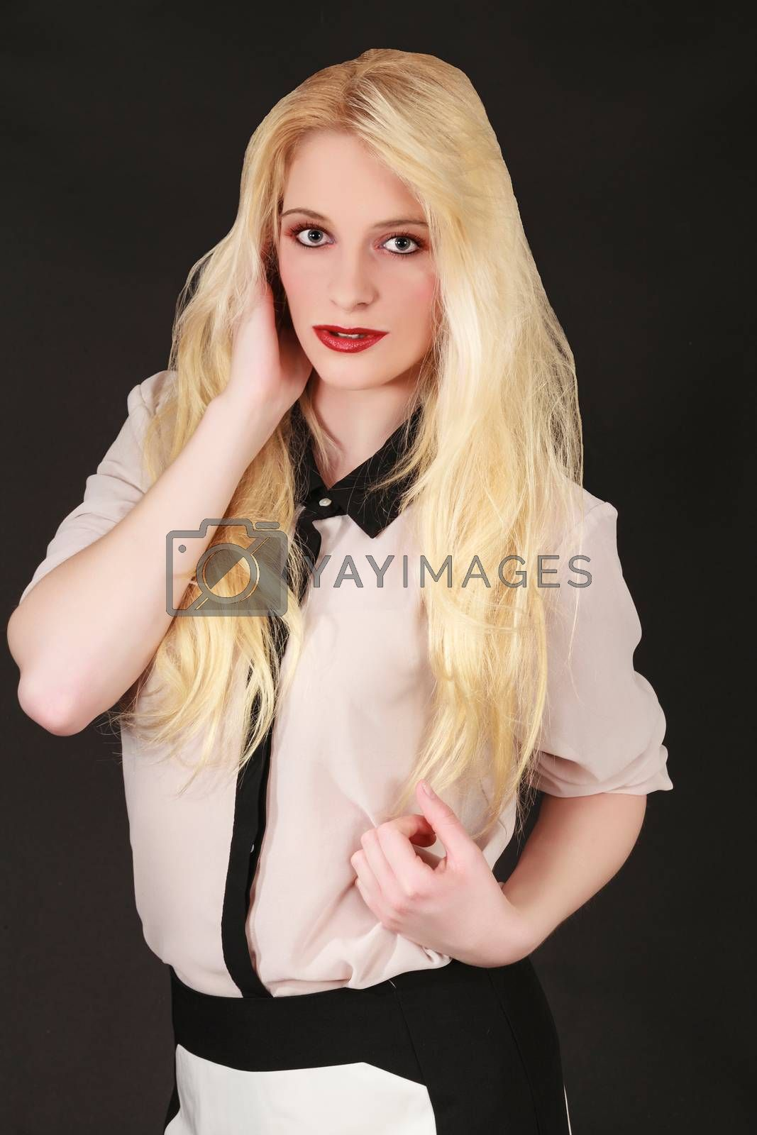 Portrait of a young blond woman with long hair, red lipstick, fashionably dressed on black background.