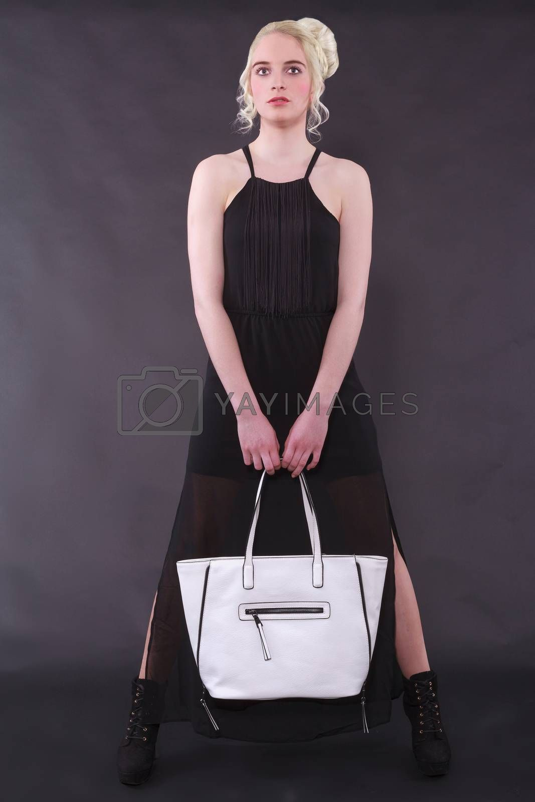 Blond young woman with modern hairstyle standing in black dress and white bag against a black background. Studio Shot.