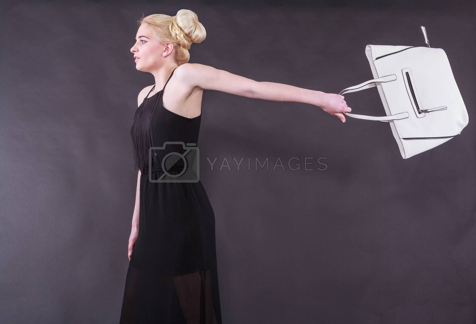 Lively young blond woman in a black dress with a white handbag on an outstretched arm back before black background, studio shot.