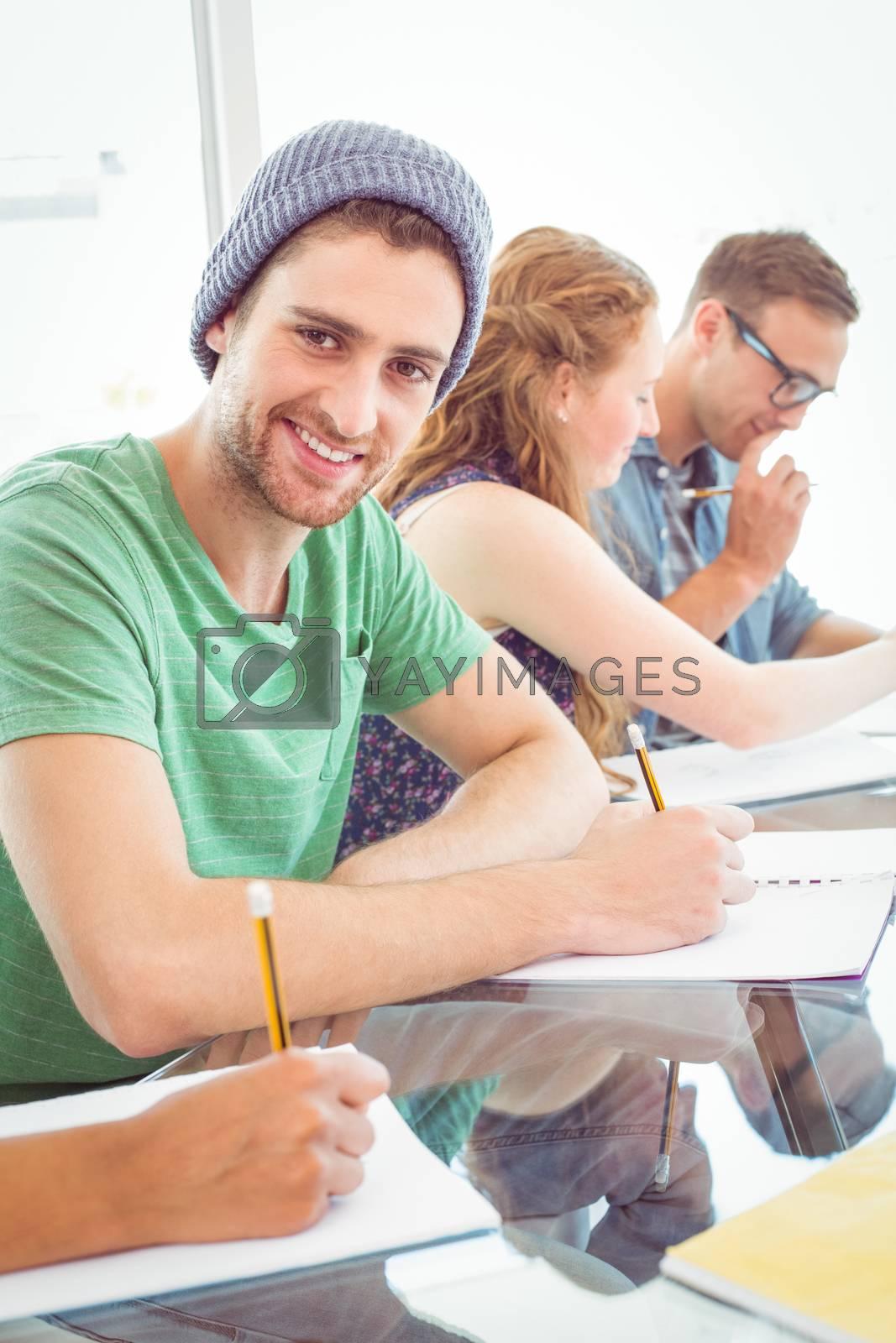 Fashion students writing on notepad  by Wavebreakmedia