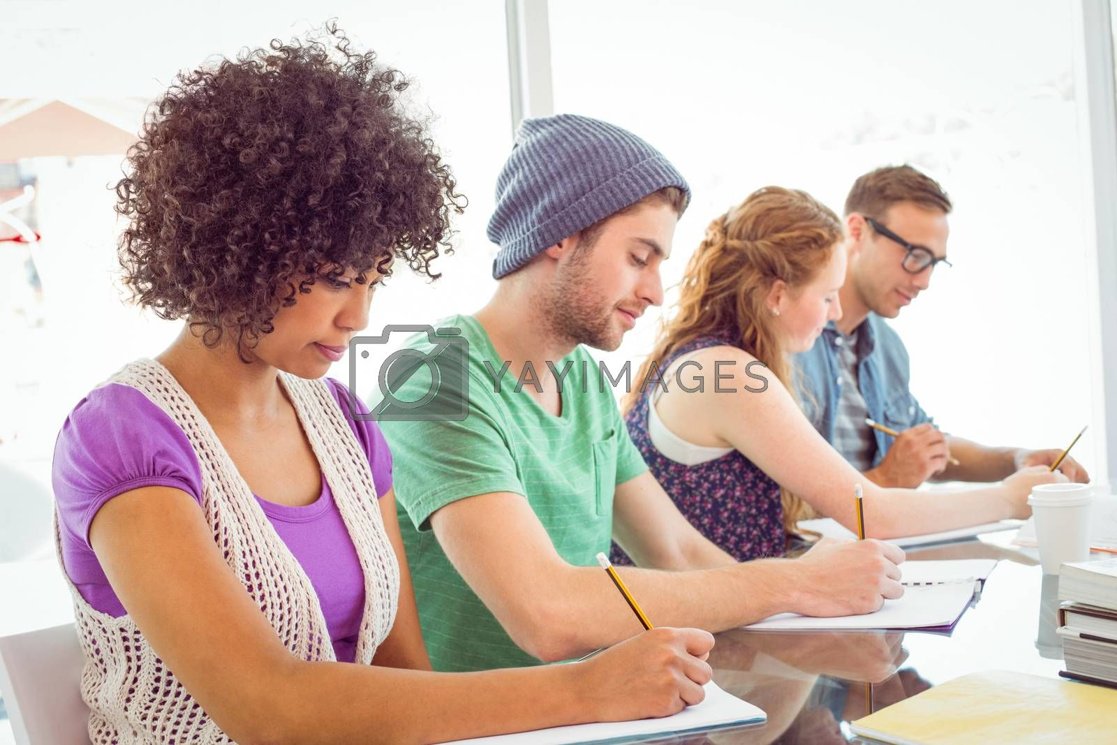 Fashion students writing on notepad  by Wavebreakmedia