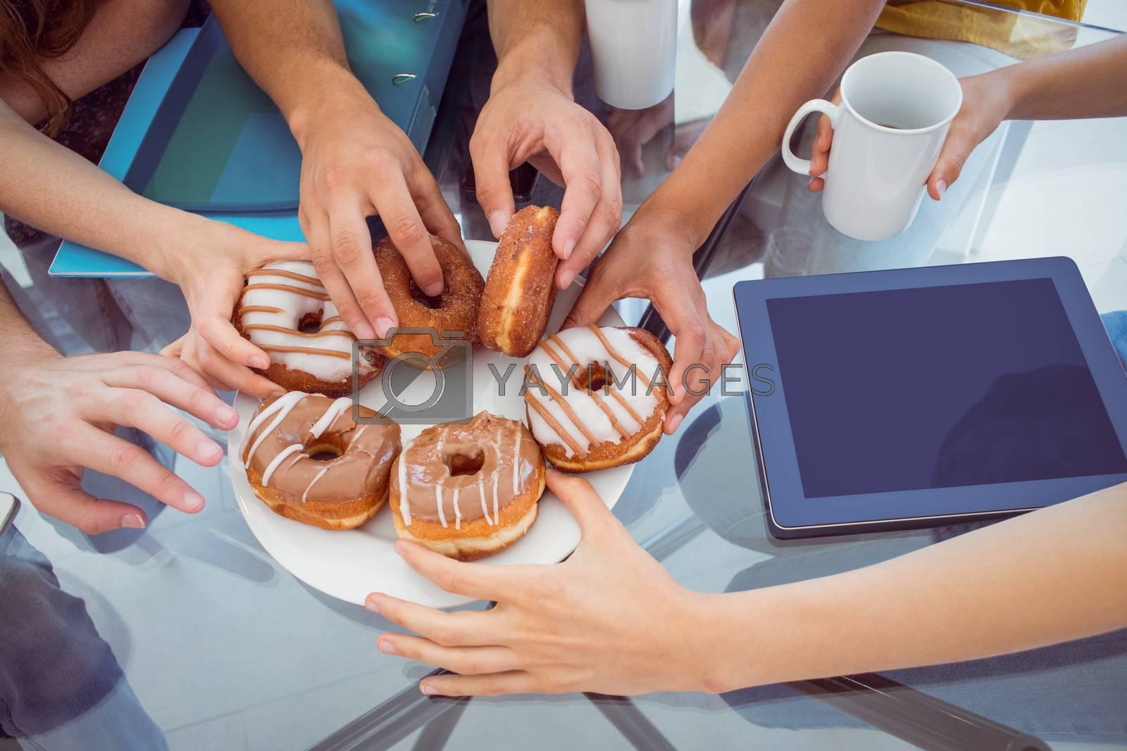 Fashion students eating doughnuts  by Wavebreakmedia
