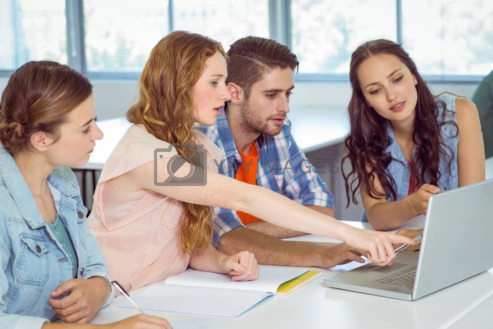 Fashion students looking at laptop at the college