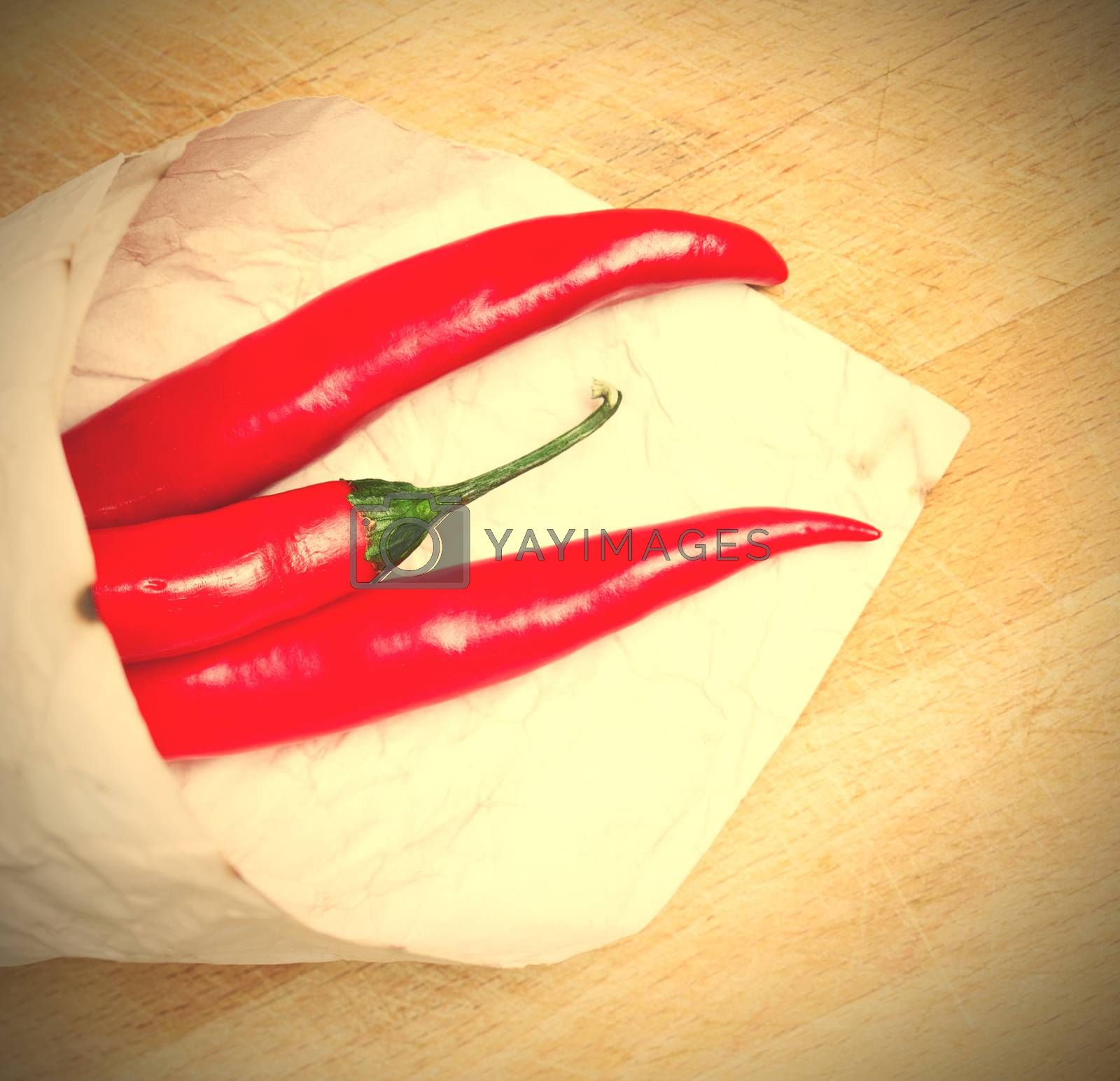 Royalty free image of red hot chili peppers in paper bags by Astroid