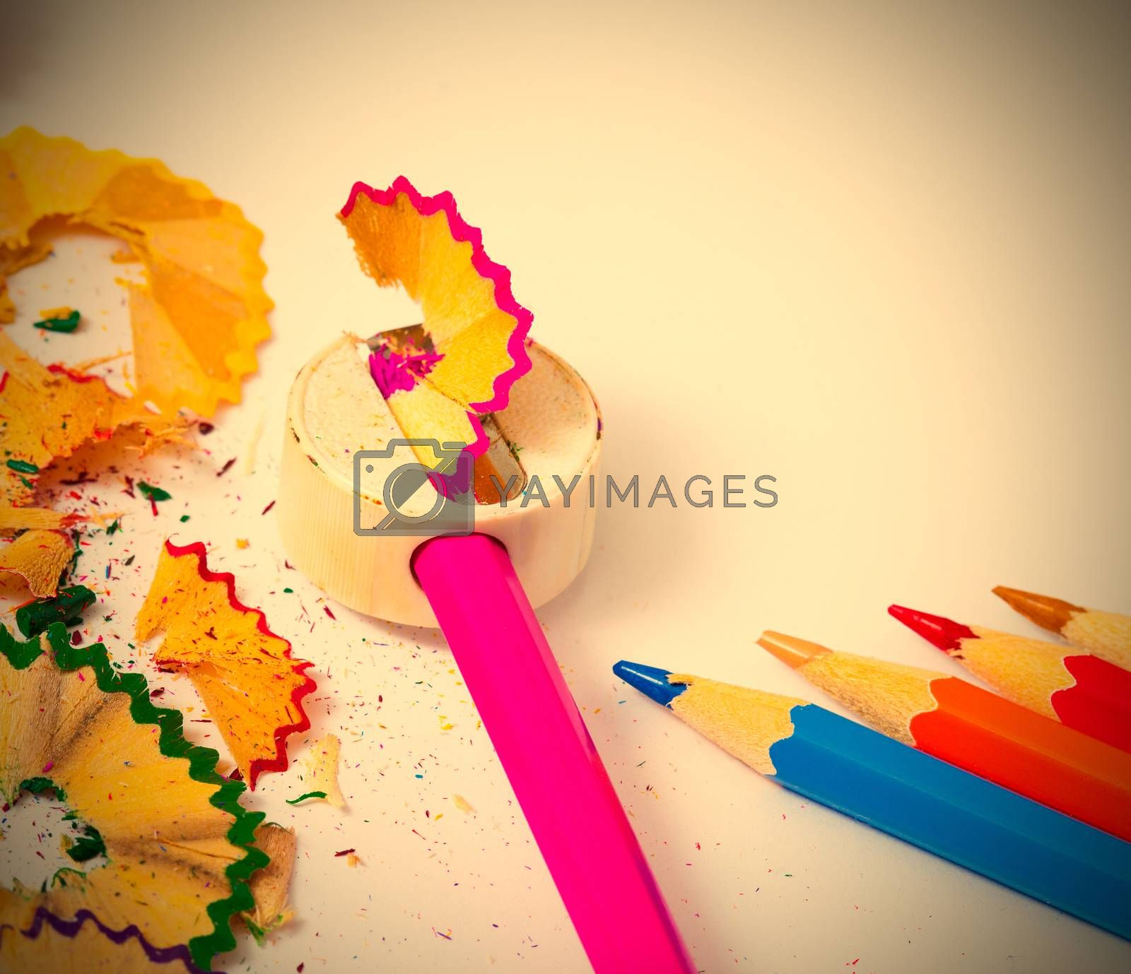colored pencils, sharpener and shavings on white background with copy space. instagram image retro style