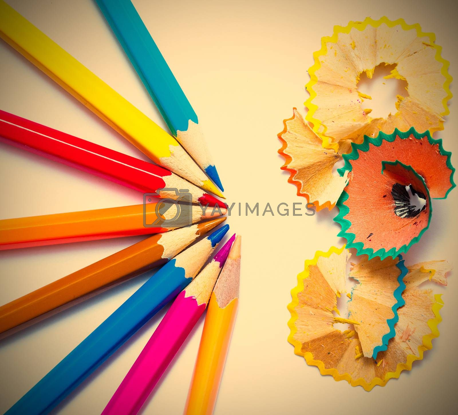 seven colored pencils and shavings on white background with copy space. insragram image retro style