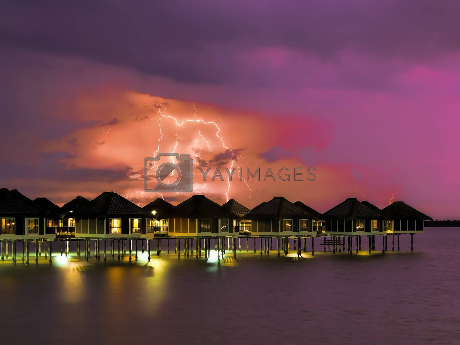 Lightning colouring the sky over water villas at night