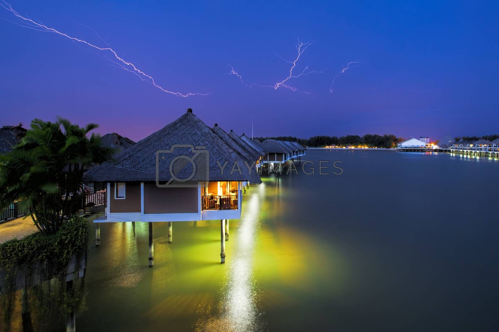 Lightning colouring the sky over waters villas at night