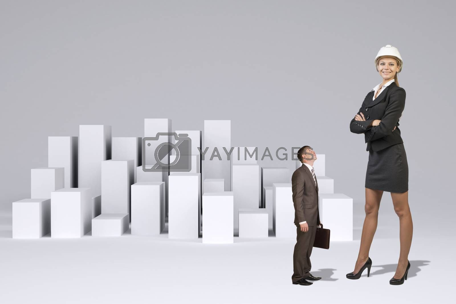 Small businessman in suit with briefcase looking at large businesswoman in suit and helmet. Many white cubes as backdrop