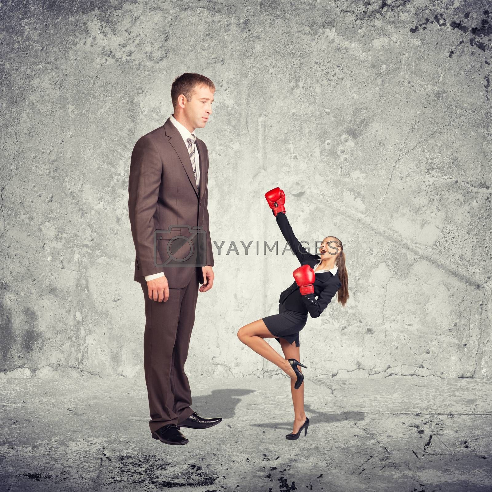 Large businessman in suit looking at small businesswoman in suit and boxing gloves. Concrete wall as backdrop