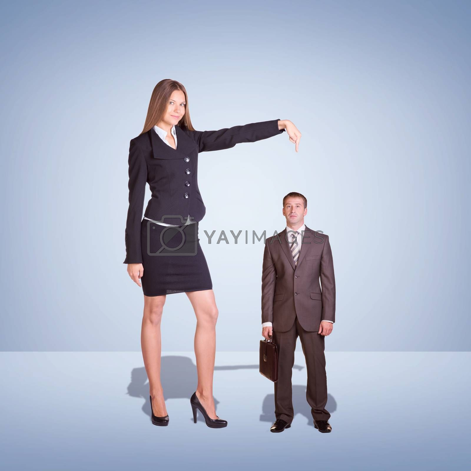 Smiling Young Businesswoman Pointing to small Businessman. Blue background