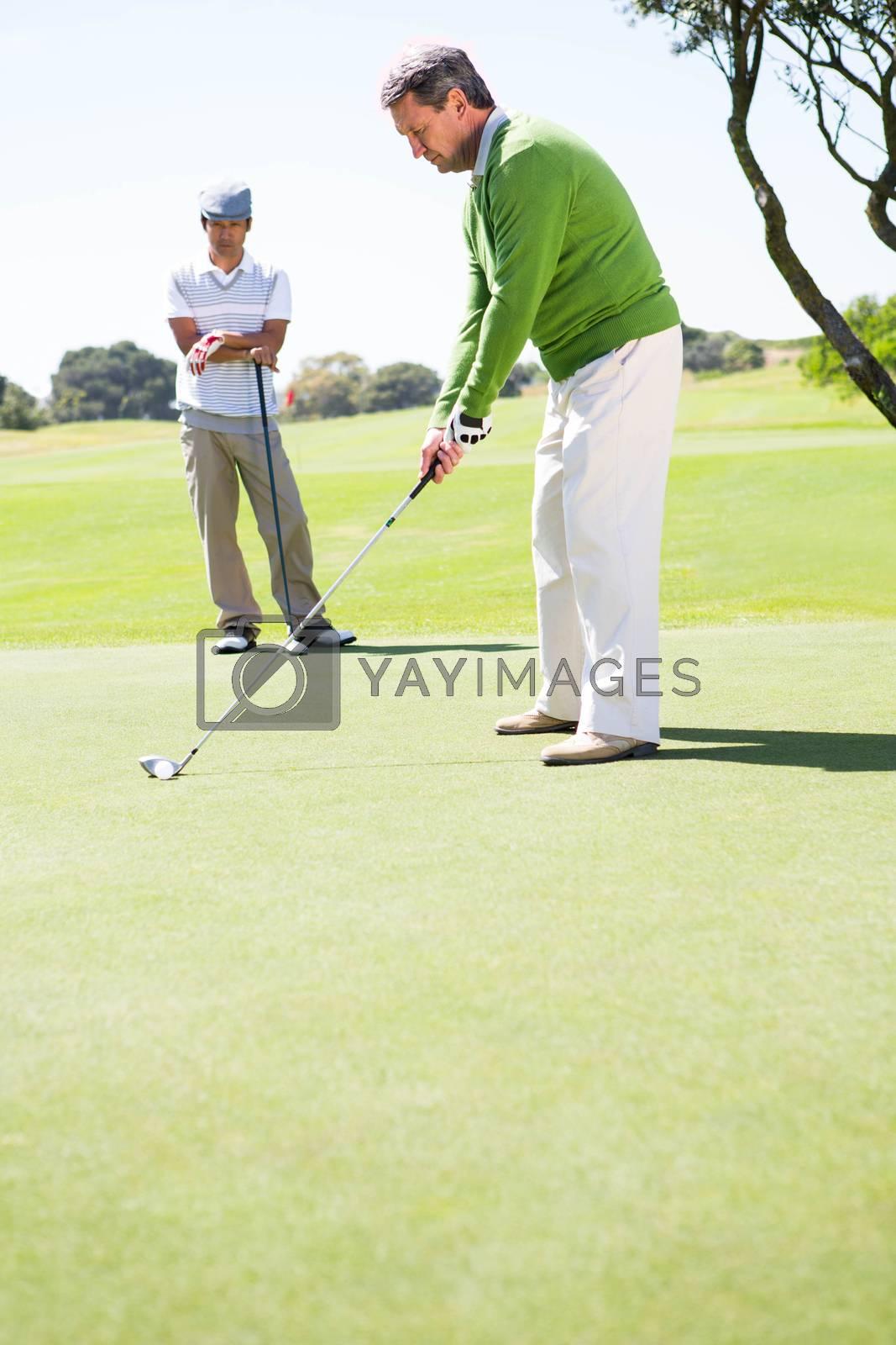 Golfing friends teeing off  by Wavebreakmedia