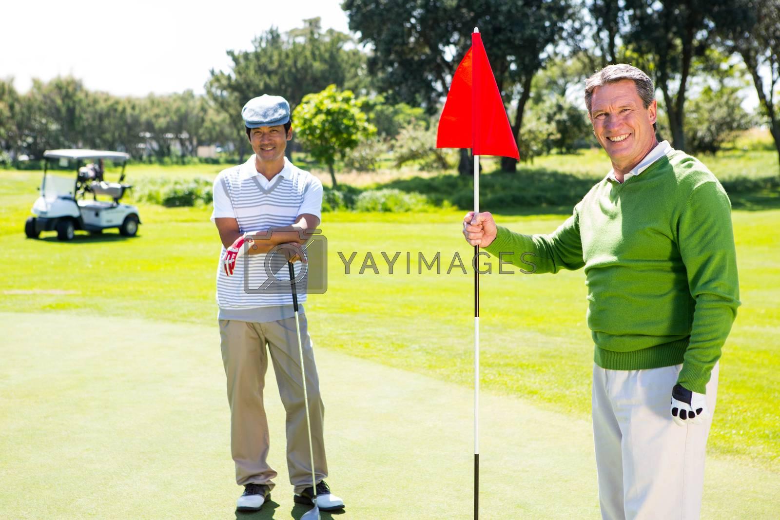 Golfing friends smiling at camera  by Wavebreakmedia