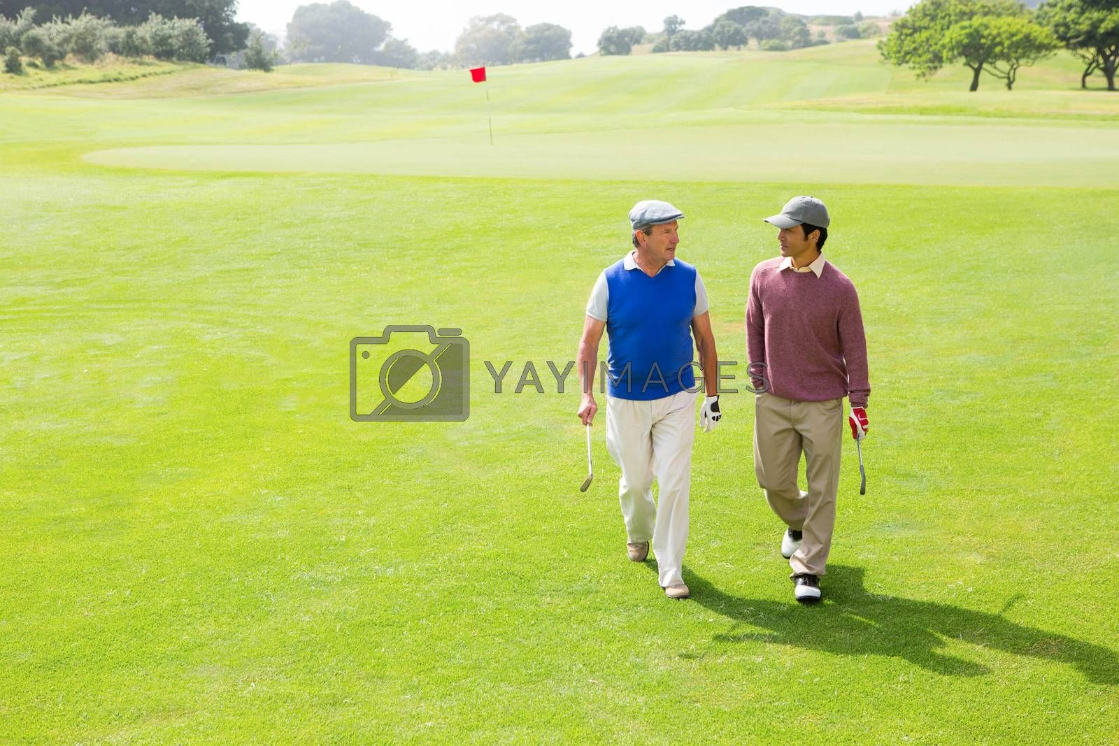 Golfer friends walking and chatting by Wavebreakmedia