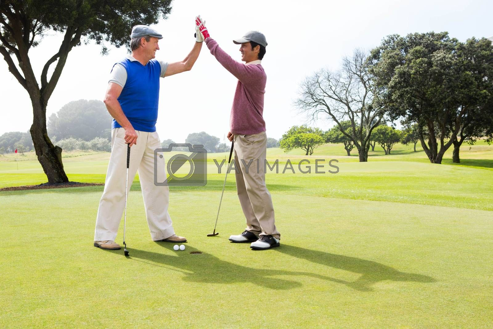 Golfing friends high fiving on the hole at the golf course