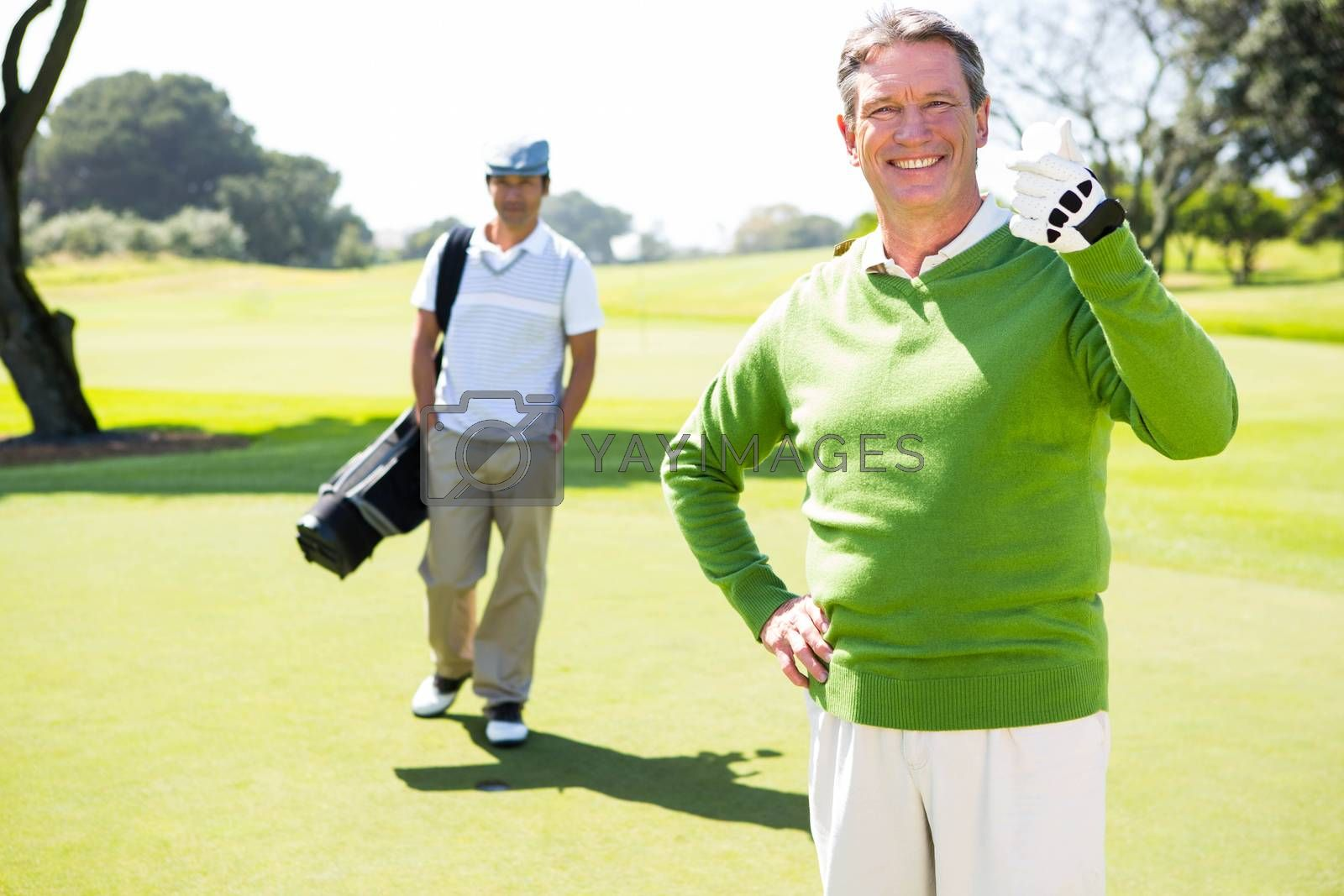 Golfing friends smiling at camera  by Wavebreakmedia