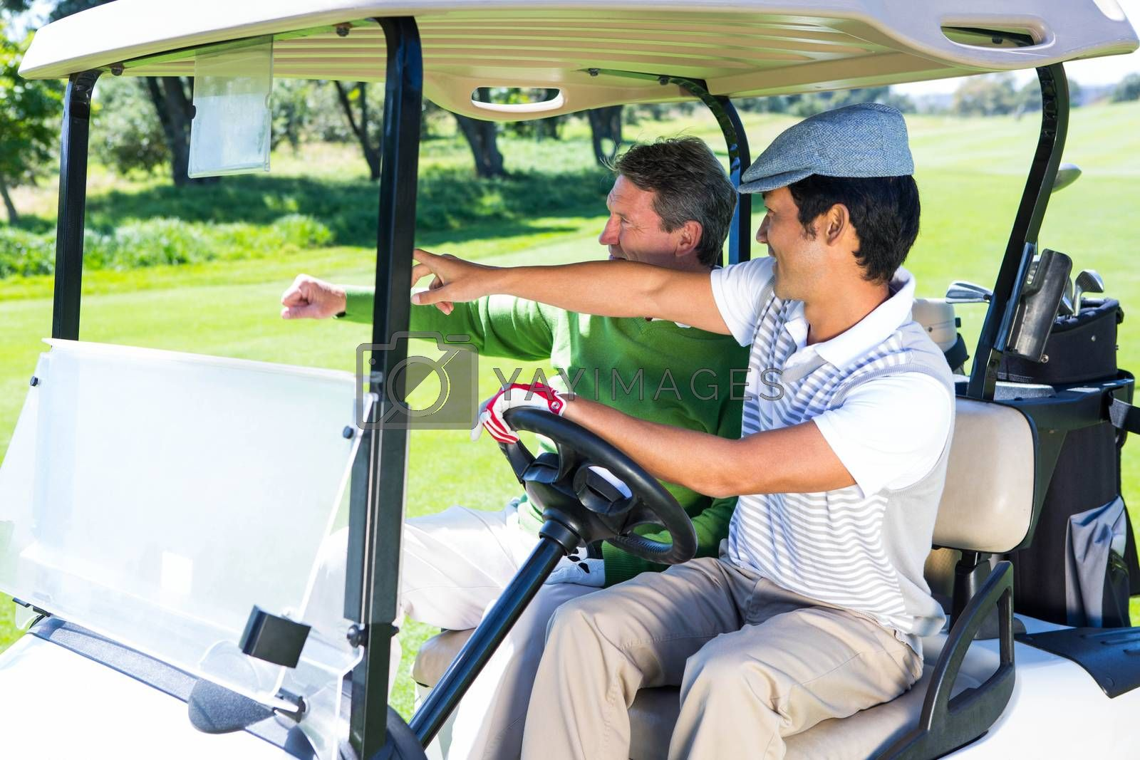 Golfing friends driving in their golf buggy by Wavebreakmedia