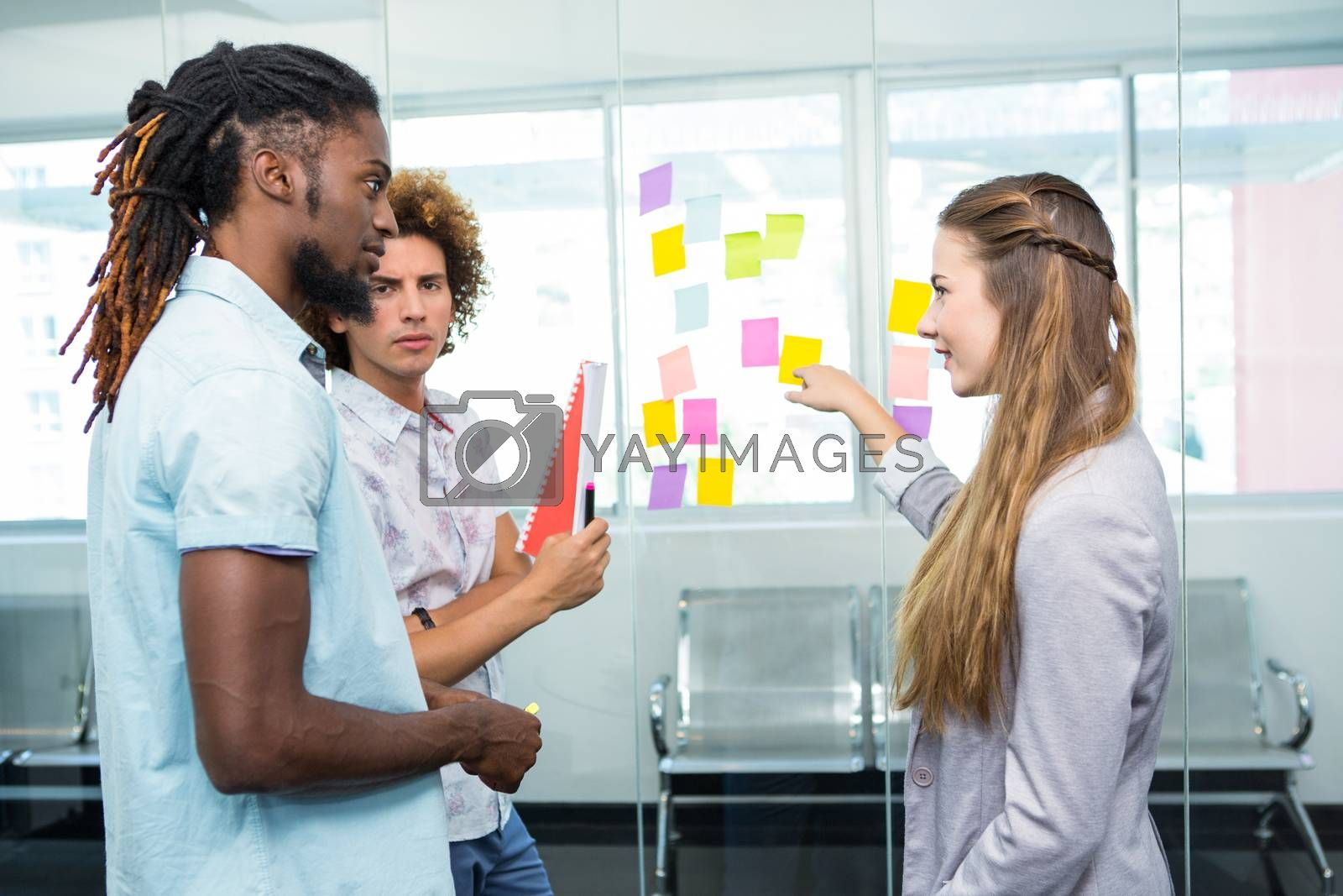 Creative business team pointing at adhesive notes in office