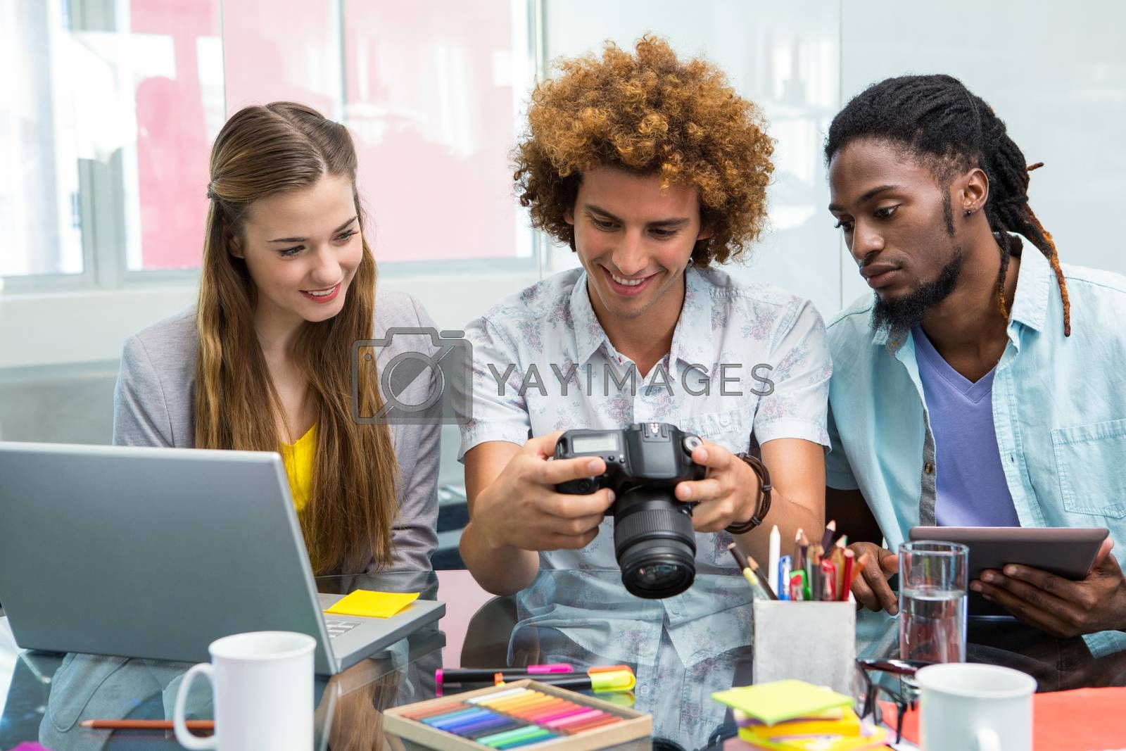 Creative young business people looking at digital camera at office desk