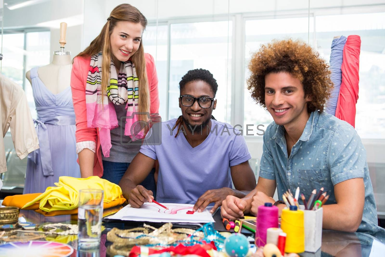 Team of young fashion designers sketching at table