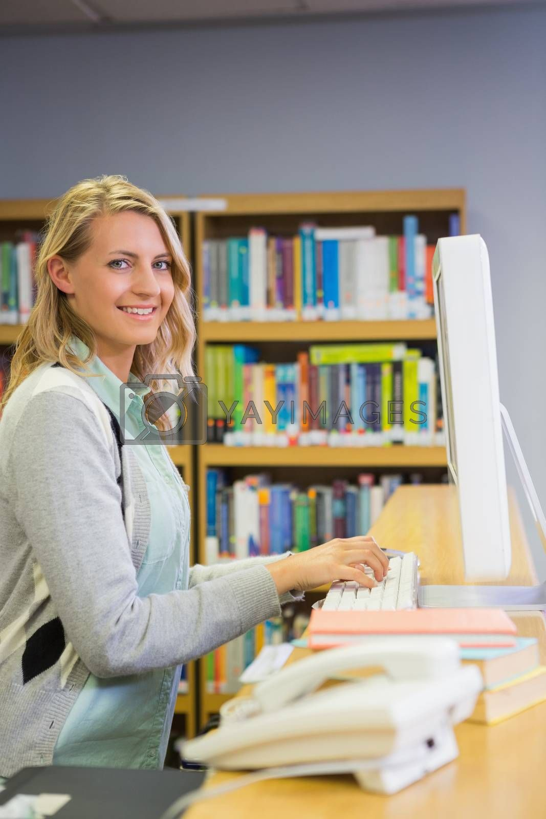Pretty librarian working in the library by Wavebreakmedia