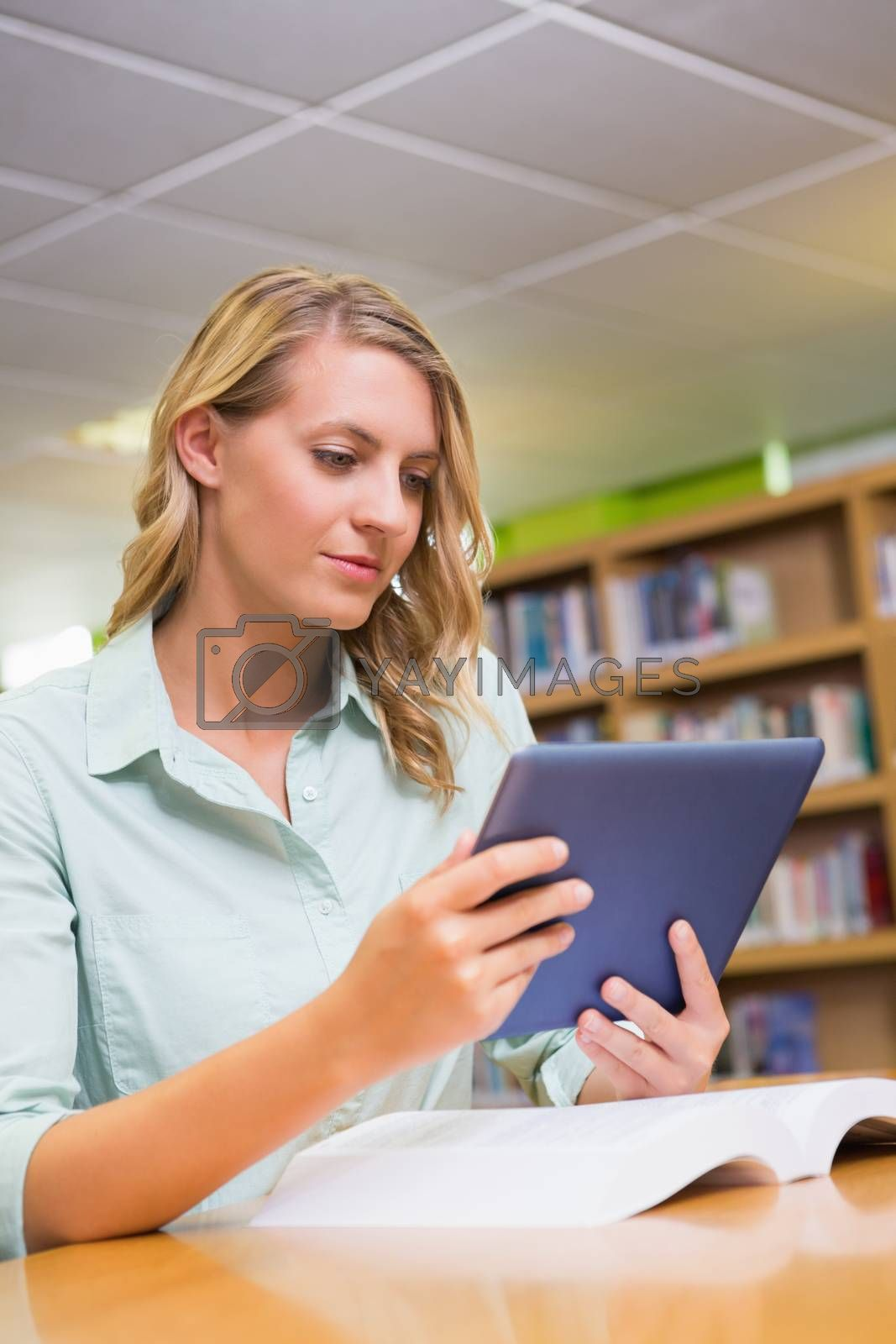 Pretty student studying in the library with tablet by Wavebreakmedia