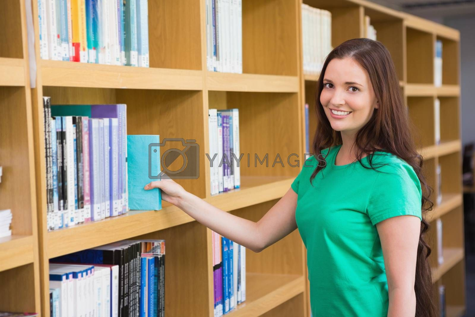Student picking a book from shelf in library by Wavebreakmedia
