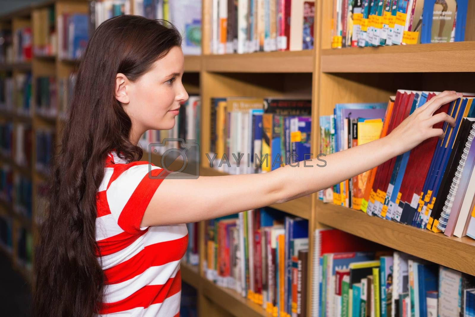 Pretty student taking book from shelf in library by Wavebreakmedia