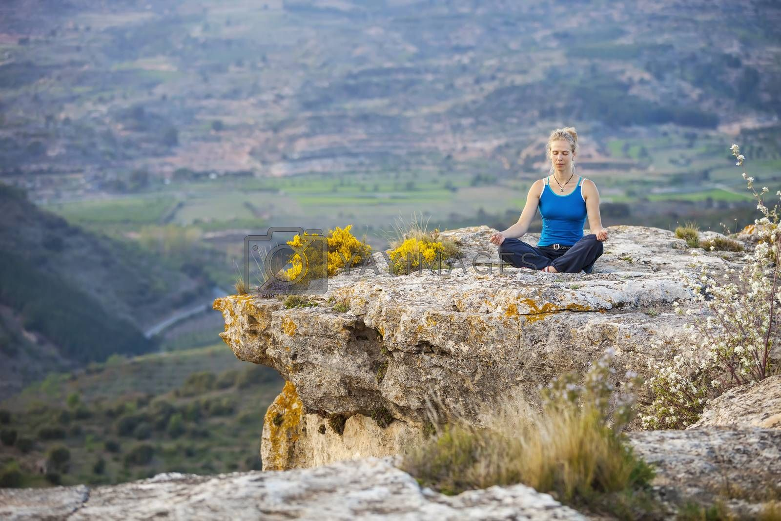 Young woman sitting on a rock and enjoying valley view. Girl sits in asana position.