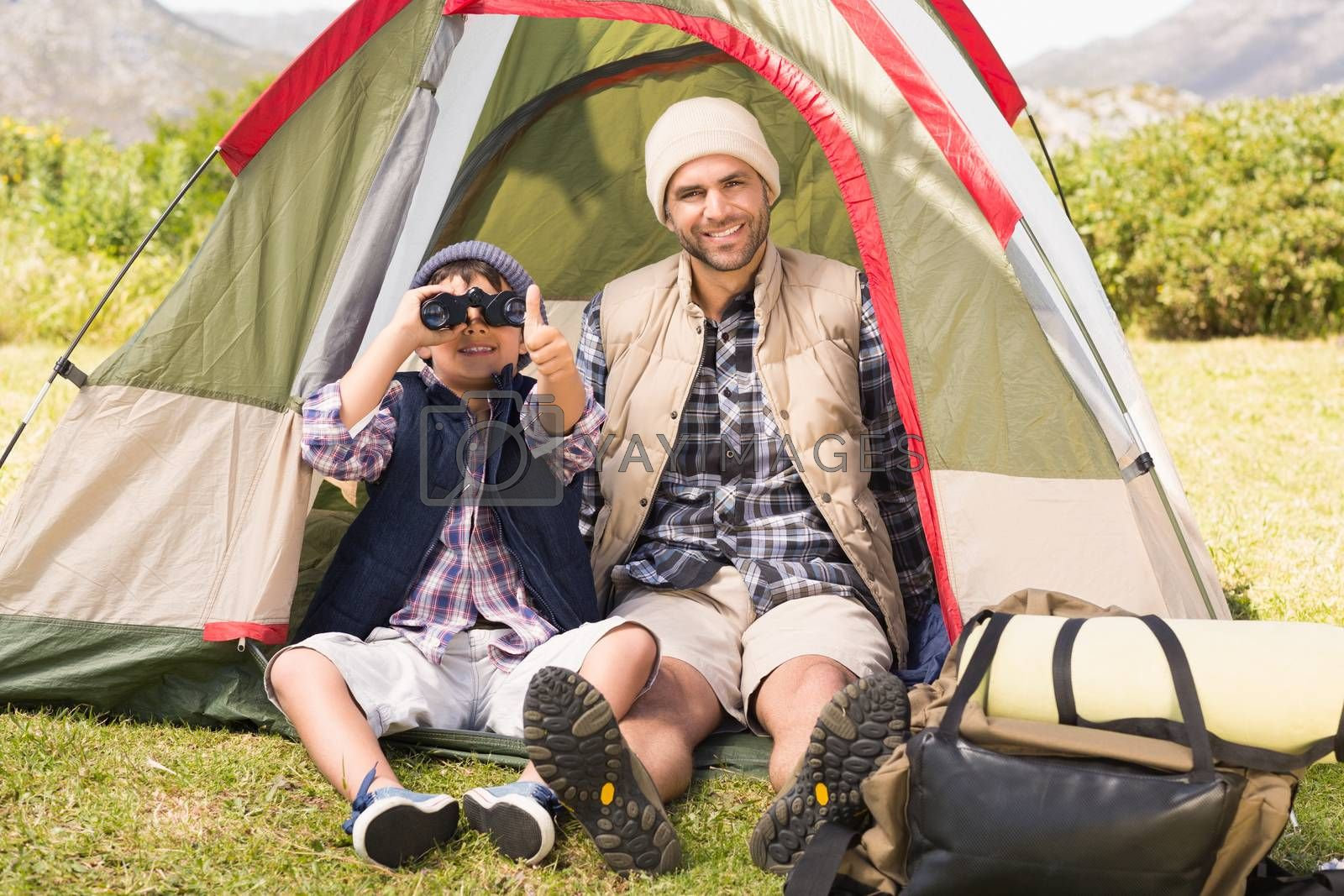 Father and son beside their tent by Wavebreakmedia