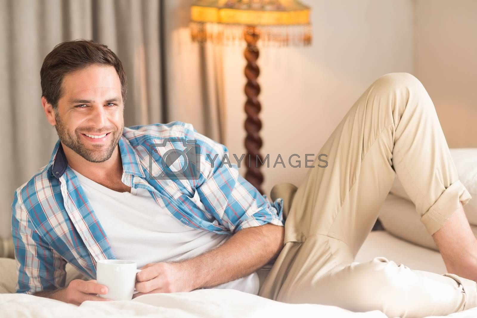 Handsome man relaxing on his bed with hot drink by Wavebreakmedia