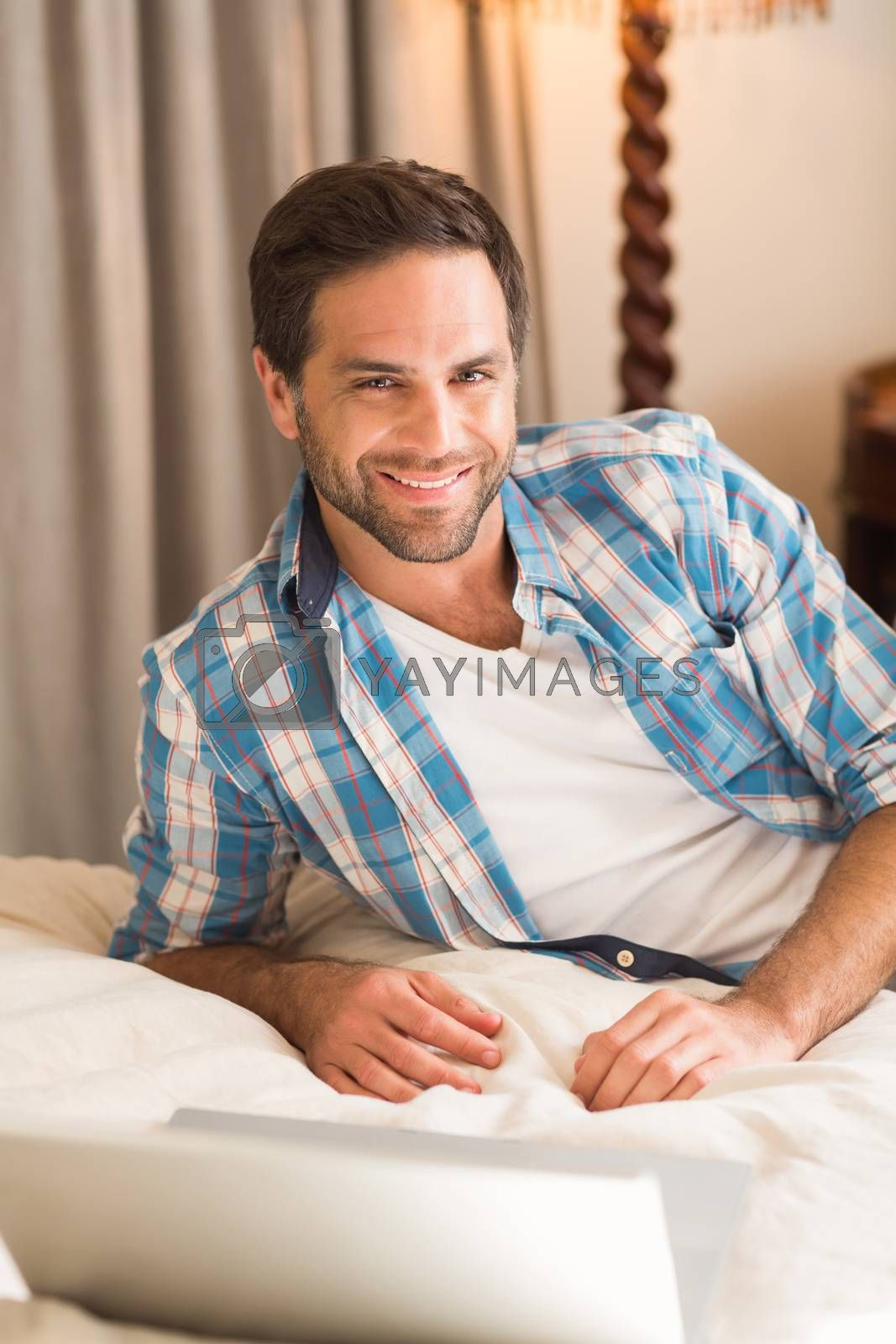 Handsome man relaxing on his bed with laptop by Wavebreakmedia