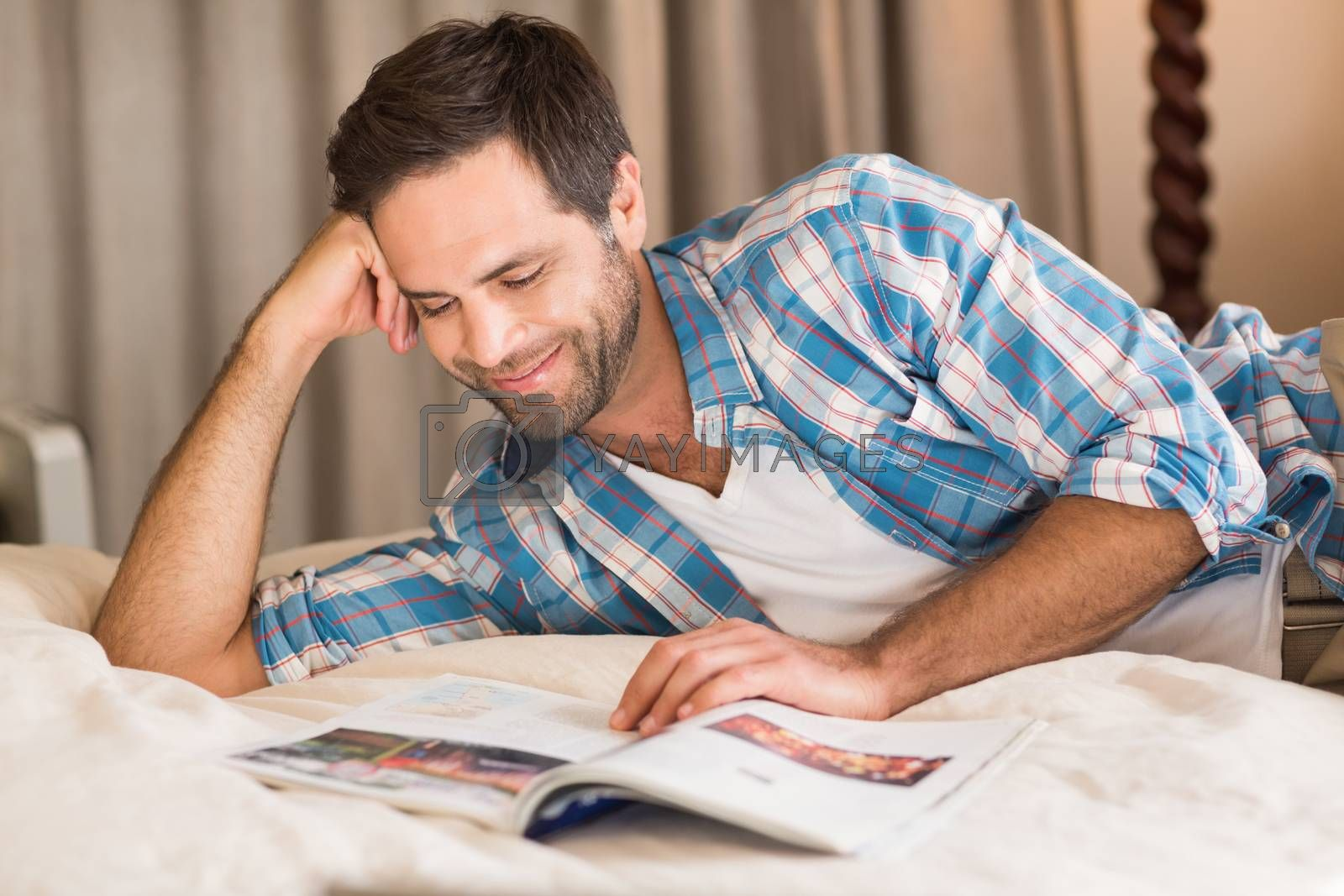 Handsome man relaxing on his bed reading magazine by Wavebreakmedia